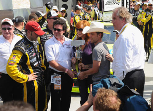 Slide 1 of 127: 2011 Brickyard 400 winner Paul Menard (C) poses with (L-R) team owner Richard Childress, CEO and President of Big Machine Records Scott Borchetta, winning team cheif, singer Reba McEntire, musician Justin Moore and Indianapolis Motor Speedway president Jeff Belskus in Victory Lane at the Brickyard 400 presented by BigMachineRecords.com at Indianapolis Motorspeedway on July 31, 2011 in Indianapolis, Indiana.