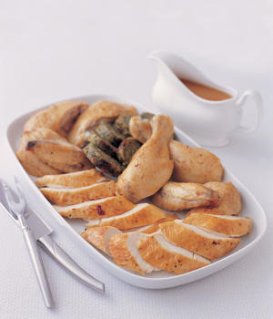 Photo: Serving roast chicken - After carving your chicken, arrange it on a hot serving plate or platter, along with any stuffing, ready for serving at the table. Pour the hot gravy into a serving dish.