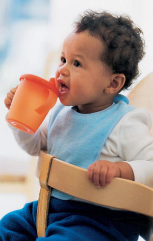 Photo: Introducing a cup - At six to eight months, you can start offering your child diluted 100 percent fruit juice or water in a sturdy cup with handles that she can hold herself.