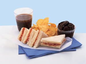 Photo: Unhealthy lunch - Ham and cheese are high in saturated fat, while white bread is low in fiber. Potato chips, chocolate-chip muffin, and cola add extra fat, sugar, and calories to this very unhealthy lunch.