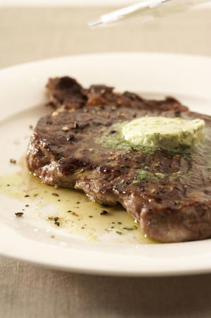 Photo: Melting flavor - As a slice of fresh herb butter melts, it creates an instant sauce, adding extra flavor to the perfectly grilled steak.