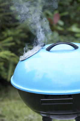 Photo: Take our advice and cover the grill only when you're doing indirect-heat grilling, like barbecuing and smoke-roasting, where the food isn't directly over the coals.