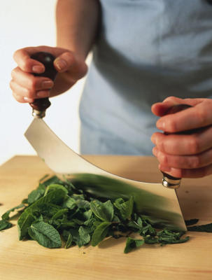 Photo: Some cooks like to use the curved mezzaluna when chopping large amounts of herbs. This implement is rocked backward and forward to great effect.