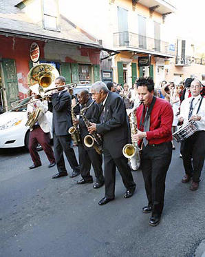 Slide 1 of 16: The Preservation Hall Jazz Band parades through the French Quarter as the famed hall reopens.