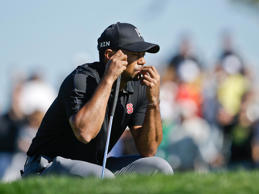 Tiger Woods waits his turn on the second green of the South Course at Torrey Pines during the Farmers Insurance Open golf tournament on Jan. 25, 2014.