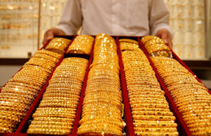File: A shop attendant displays a tray of gold bangles for the camera at a jewellery store in Singapore September 18, 2008.