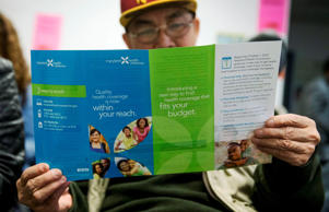 Sakoun Khanthanoua reads a Maryland Health Connection health insurance pamphlet in Silver Spring, Maryland.