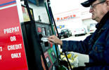 A customer swipes his card as he prepares to fill his truck with fuel at a gas station in Princeton, Illinois.