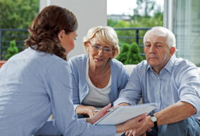 Senior couple having meeting with financial advisor at home.