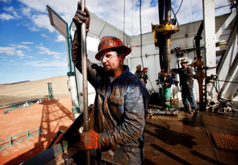 Brian Waldner is covered in mud and oil while wrestling pipe on a True Company oil drilling rig outside Watford, North Dakota.