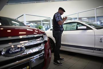 File photo of a shopper looking at a Ford Mustang on the showroom floor at a Ford AutoNation car dealership in North Miami, Florida.