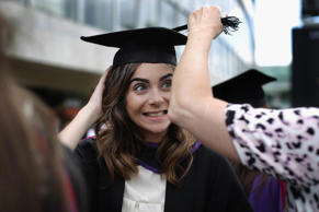 A student has her hat adjusted by her mother ahead of her graduation ceremony.