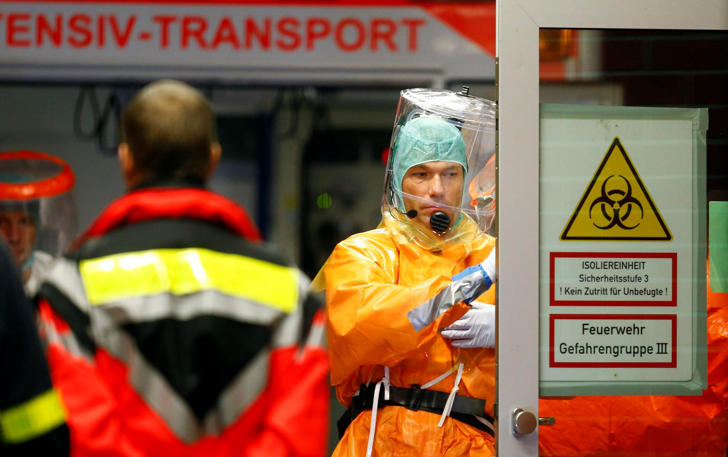 Medical staff members wearing sealed protective suits work during the arrival of an Ebola patient in Frankfurt, Germany, Oct. 3, 2014.