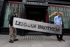 Two employees of Christie's auction house take the Lehman Brothers corporate logo away in 2010.