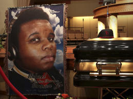 A baseball cap and a portrait of Michael Brown is shown alongside his casket inside Friendly Temple Missionary Baptist Church before the start of funeral services in St. Louis, Missouri, August 25, 2014.  Family, politicians and activists gathered for the funeral on Monday following weeks of unrest with at times violent protests spawning headlines around the world focusing attention on racial issues in the United States.