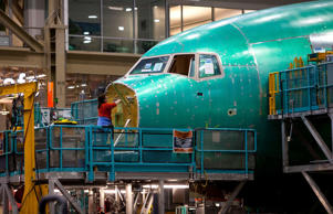 An employee works on the nose of a Boeing Co. 777 airplane at the company's facility in Everett, Washington, on June 25, 2013.