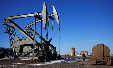 A man walks onto an oil drilling pump site in McKenzie County outside of Williston, North Dakota March 12, 2013. Shannon Stapleton/Reuters