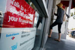 A sign advertises home mortgage services as a customer enters a Bank of America Corp. branch in Manhattan Beach, California, U.S., on Tuesday, Sept. 10, 2013. Mortgage applications in the U.S. plunged last week to the lowest level in almost five years as rising borrowing costs led to a slump in home refinancing.