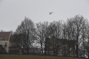 A helicopter of the French gendarmerie flies over Dammartin-en-Goele, where shots were fired and at least one hostage was taken, in the same area police were hunting for two brothers accused of slaughtering 12 people in an assault, on January 9, 2015.