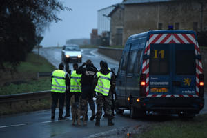 Police officers stop a car at a check point on Jan. 9, 2015, outside Longpont, France.