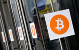 Bitcoin logos are displayed at the Inside Bitcoins conference and trade show, Monday, April 7, 2014 in New York.