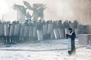 A priest is seen praying even as riot police stand guard in Kiev, Ukraine in January 2014. Thousands protested against the government as President Viktor Yanukovych discussed a new strategic partnership agreement with Russia's Vladimir Putin upon rejecting a historic EU deal. Yanukovych was ousted from power soon after.