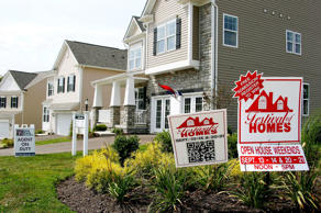 In this photo made on Wednesday, Sept. 10, 2014, signs welcome visitors to a model home as construction is under way at a housing development in Zelienople, Pa. Average long-term U.S. mortgage rates rose slightly this week but remained near their lows for the year.