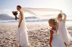 Bride and flower girls on beach