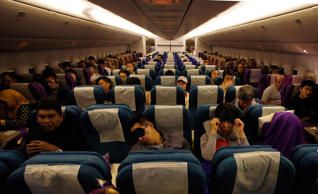 Passengers in their seats onboard a flight traveling toward Beijing.