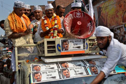 File: Arvind Kejriwal (wearing garlands), the leader of the anti-corruption Aam Aadmi Party (AAP), stands atop a vehicle after ink was hurled at him and other party workers during a public rally ahead of the general elections in Varanasi, in the northern Indian state of Uttar Pradesh, March 25, 2014.