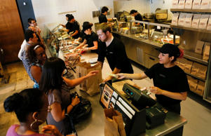 An employee rings up a customer while others prepare orders at a Chipotle Mexican Grill Inc. restaurant in Hollywood, California on Tuesday, July 16, 2013.