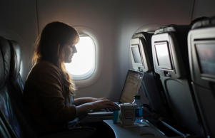 A woman uses the new high speed inflight Internet service named Fli-Fi while on a JetBlue flight out of John F. Kennedy International Airport in New York December 11, 2013.