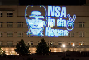 The facade of the US embassy is illuminated with a light installation by German artist Oliver Bienkowski showing an image of President Barack Obama wearing a baseball cap and reading 'NSA in da House' in Berlin.