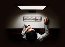 Man sitting at glowing computer screen in darkness.