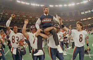Chicago Bears head coach Mike Ditka is carried off the field by Steve McMichael, left, and William Perry after the Bears win Super Bowl XX in New Orleans, La., on Jan. 26, 1986.  The Bears' Willie Gault (83) and Maury Buford (8) join in celebrating their 46-10 victory over the New England Patriots.