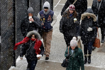 A light snow falls on pedestrians, Monday, Jan. 26, 2015 in New York. The National Weather Service says accumulations of 18 to 24 inches are possible by Tuesday afternoon. Mark Lennihan/AP
