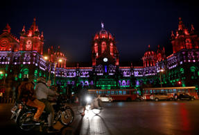 File: Commuters move past the Chhatrapati Shivaji train station building illuminated with the three colors of the Indian flag on Republic Day in Mumbai, India, Monday, Jan. 26, 2015.