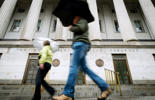 Pedestrians walk past the U.S. Treasury Building on a rainy day in Washington, Thursday, Oct. 10, 2013.