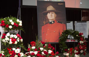 A photo of slain RCMP Constable David Wynn stands amongst flowers during his funeral procession.