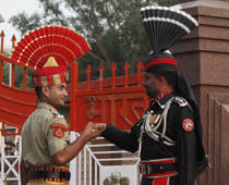 File: A Pakistani Ranger (R) and an Indian Border Security Force (BSF) officer shake hands during the daily parade at the Pakistan-India joint check-post at Wagah border, on the outskirts of Lahore October 23, 2011.