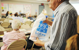 "A retiree carries a bag of educational pamplets from L.A. Care, the largest public health plan in the US, at a Senior Information & Resource Fair in South Gate, California September 10, 2013 . The event included a discussion of how the Affordable Care Act, also called ""Obamacare"" will impact senior citizens and what insurance plans will be available to them.  With just weeks until a centerpiece of the health care reform law launches, the task of spreading the word about new health insurance marketplaces will fall to local navigators and counselors employed locally but funded by federal grant money."