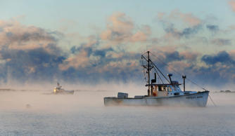 A rising sun colors sea smoke rising around lobster boats in Cape Porpoise harbor on Thursday, January 8, 2015.