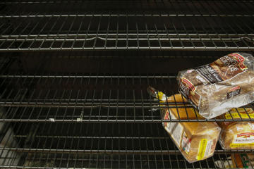 Loaves of bread sit on a sparse shelf of bread items at a grocery store in Port Washington, New York January 26, 2015.