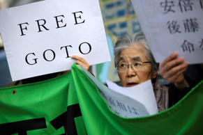 "A woman along with other protesters hold a placard and chant ""Free Goto"" during a rally outside the prime minister's official residence in Tokyo on Jan. 27, 2015."