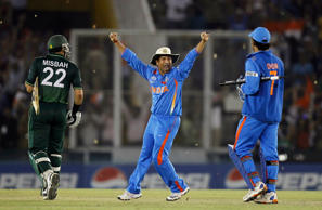 India's Sachin Tendulkar celebrates with captain and wicketkeeper Mahendra Singh Dhoni as Pakistan's Misbah-ul-Haq walks off the field after India won their ICC Cricket World Cup 2011 semi-final match in Mohali March 30, 2011.