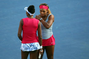 Venus Williams (USA) and Serena Williams (USA) during a match against Oksana Kalashnikova (GEO) and Olga Savchuk (UKR) on Armstrong Stadium on day five of the 2014 U.S. Open tennis tournament at USTA Billie Jean King National Tennis Center.