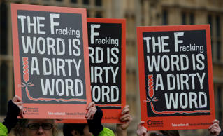 Demonstrators hold up placards as they take part in an anti-fracking protest outside the Palace of Westminster in London, Monday, Jan. 26, 2015.
