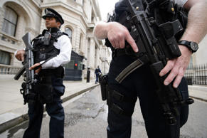 Armed police officers hold guns as they stand in Downing Street, in central London