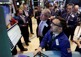 Specialist Paul Cosentino, foreground center, works at the post that handles Cliffs Natural Resources, on the floor of the New York Stock Exchange Tuesday, Jan. 27, 2015. U.S. stocks are tumbling in midday trading, weighed down by disappointing forecasts from big-name companies and an unexpected drop in orders of long-lasting goods.