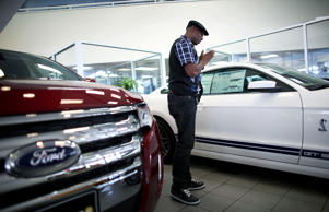 Anthony Gordon looks at a Ford Mustang on the showroom floor at a Ford AutoNation car dealership in North Miami, Florida.